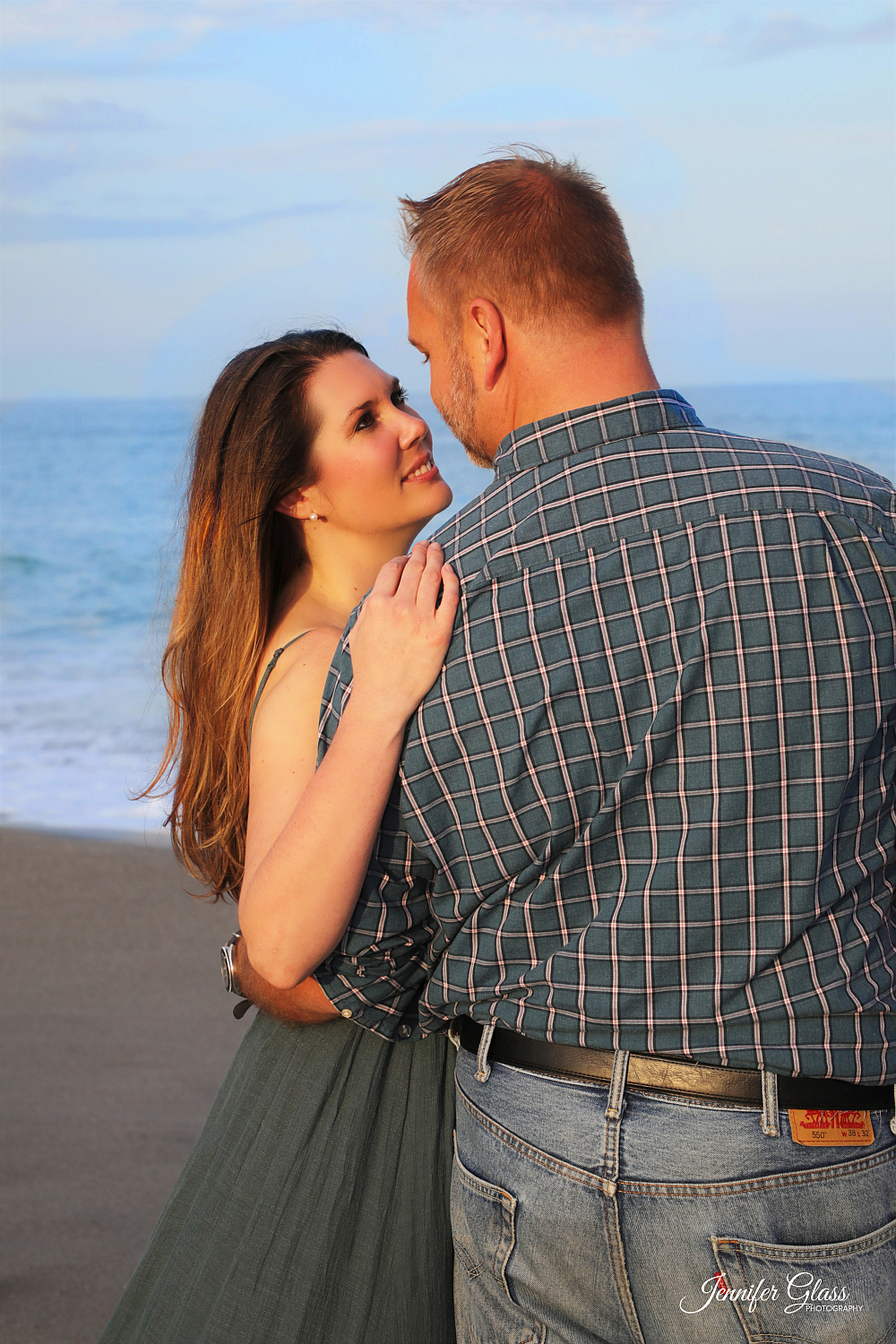 man and woman embrace on beach Photo