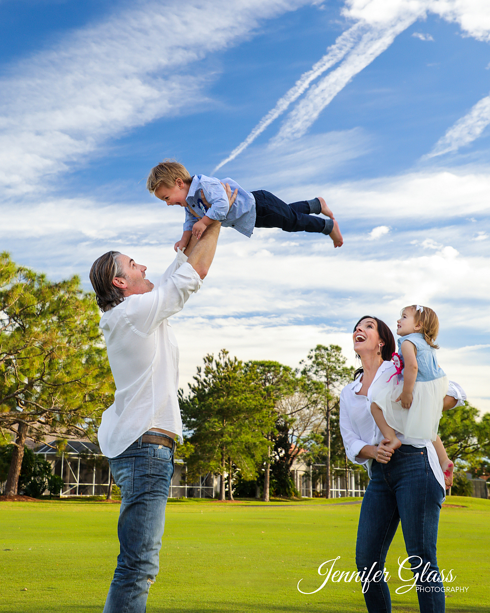 man swings young boy up high family laughing Photo